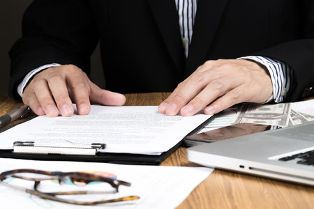 businessman hand checking marketing document Standard-Bild