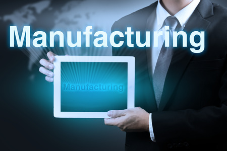 life cycle: businessman holding tablet showing word MANUFACTURING on virtual screen.