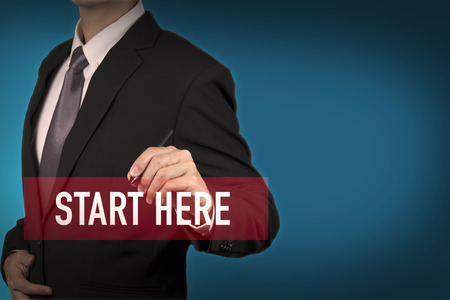 Businessman write Start here word for stat to success in business position. Archivio Fotografico