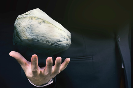 businessman hand holding a big rock Standard-Bild
