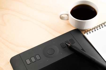 black coffee pen tablet and notebook on wooden table photo