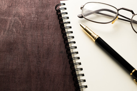 book pen and glasses on wooden table