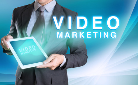 businessman holding tablet with VIDEO MARKETING word with abstract background for Business Archivio Fotografico