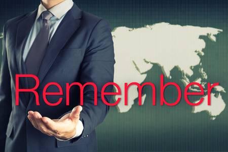 remember: Businessman show Remember word on world map background Stock Photo