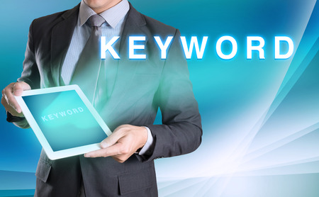 keyword: businessman holding tablet with KEYWORD word with abstract background for Business