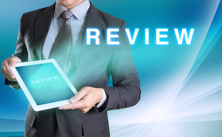 performance appraisal: businessman holding tablet with Review word with abstract background for Business Stock Photo