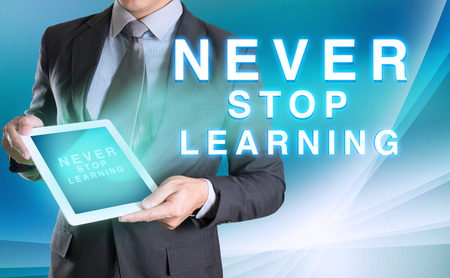 lifelong: businessman holding tablet with NEVER STOP LEARNING word with abstract background for Business