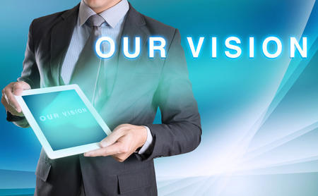 our: businessman holding tablet with OUR VISION word with abstract background for Business Stock Photo