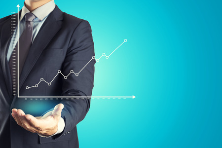 Businessman Holding investment business graph Standard-Bild