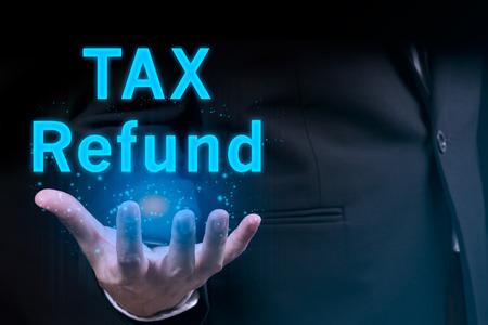 tax refund: Businessman hand holding TAX REFUND word Stock Photo