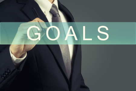 achievable: Businessman writing GOALS Word