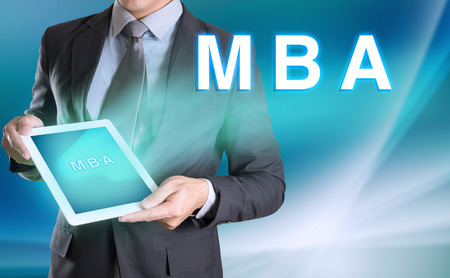 mba: businessman holding computer tablet in hand and show MBA word