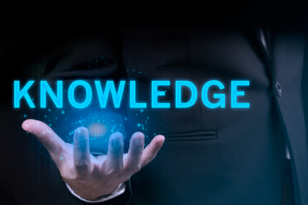 Businessman hand holding KNOWLEDGE word