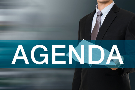meeting agenda: Businessman with AGENDA Word