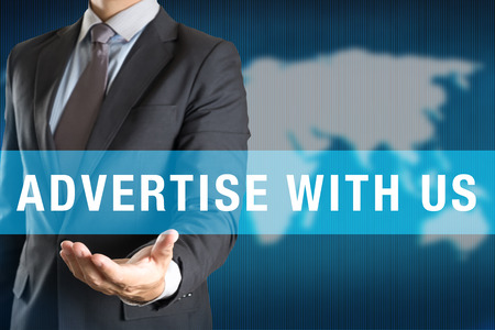 advertise: Businessman holding ADVERTISE WITH US word with world background