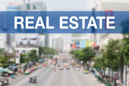 press agent: Blur city background with REAL ESTATE Word Stock Photo