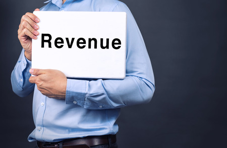 tax bracket: Businessman holding white board with REVENUE WORD Stock Photo
