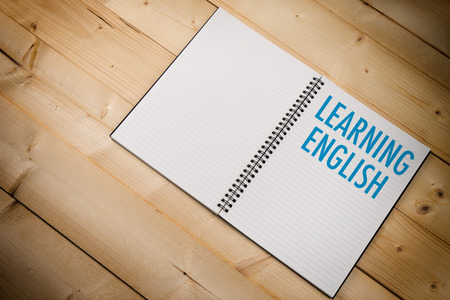 english text: LEARNING ENGLISH text on Writing-book over wood table background Stock Photo