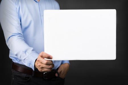 bonhomme blanc: Homme d'affaires tenant un tableau blanc blanc pour copie espace Banque d'images