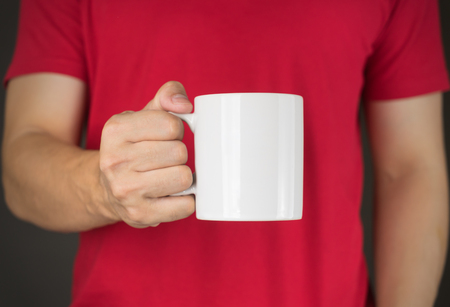 red tshirt: Man in red t-shirt holding Coffee mug Stock Photo
