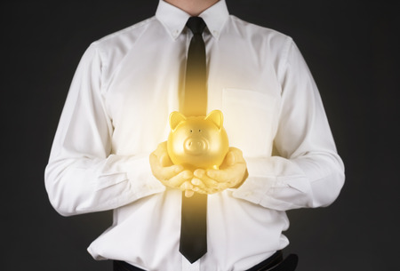 shiny suit: A Man Holding a  Gold piggy bank for Saving money.