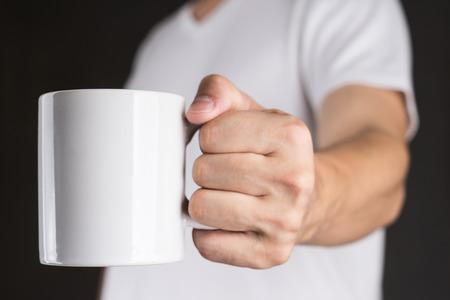 커피 잔을 들고 흰색 티셔츠에있는 남자