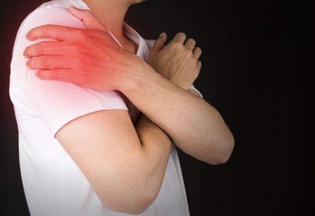 seniors suffering painful illness: Man in white t-shirt with pain in shoulder Stock Photo