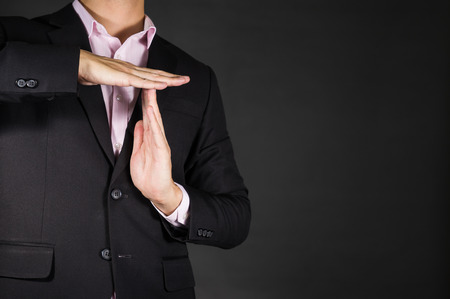 body language: Businessman showing a pause time out gesture with hands. body language signs symbols
