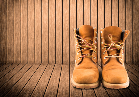 missionary: man boot adventure on wood texture background