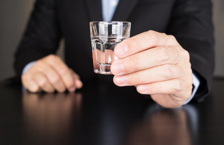vodka: Businessman holding glass of vodka Stock Photo