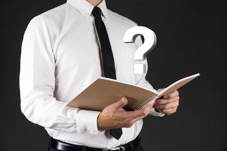 hidden success: Businessman Holding book with Question mask