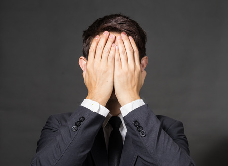 Businessman covering his face with hand Standard-Bild
