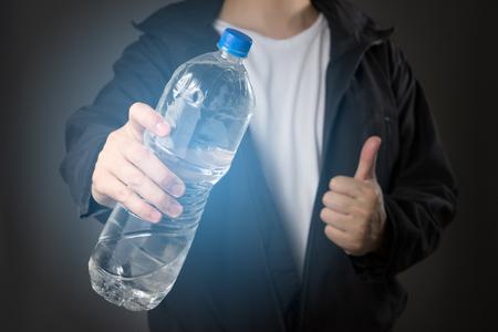 黒のジャケットと黒の背景の上に水の新鮮なボトルを保持している白い t シャツの男性 写真素材