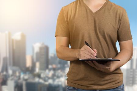 クリップボードに調査をペンと塗りつぶしを保持している茶色の t シャツの男性。市内での調査にフォーカス。