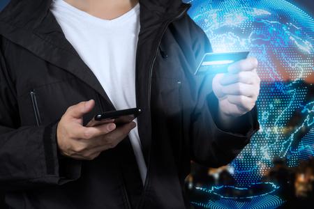 グローバル スマート フォンと仮想オンライン ショッピングにクレジット カードを保持してアジアの男