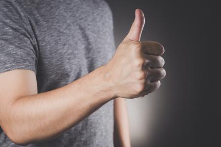 中略サインアップのグレーの t シャツを親指でアジア人男性は、ビンテージ写真の同意サイン フィルター スタイル