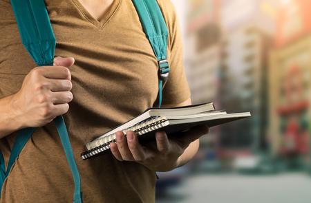 茶色の t シャツ開催アジア男研究本とぼかし街背景に学校や大学に行く準備ができてする緑色の袋をカード 写真素材