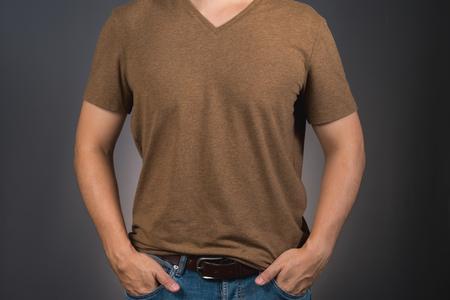 アジア男ポーズ コピー スペースと茶色の t シャツ