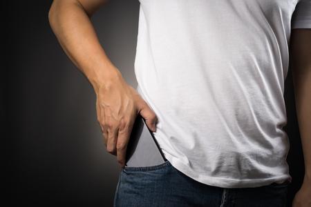 白い t シャツの男性がジーンズのスマート フォンを拾う