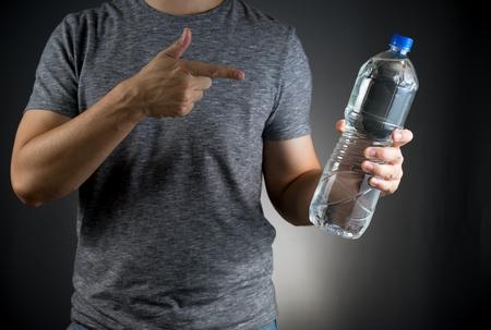 新鮮な水のボトルを押しながらそれを指しているグレーの t シャツの男性 写真素材