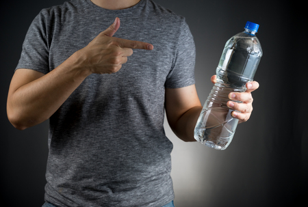 asian man on gray t-shirt holding a fresh water Bottle and pointing on it