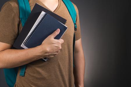 アジア学生男を運ぶバッグと大学の彼の教育のための研究本を保持しています。 写真素材