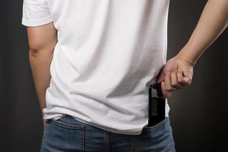 彼の友人を呼び出すにジーンズに黒いスマート フォン ピックアップ白い t シャツにアジア男