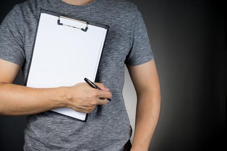 グレーの t シャツにアジア男クリップボード紙とペンを持って 写真素材