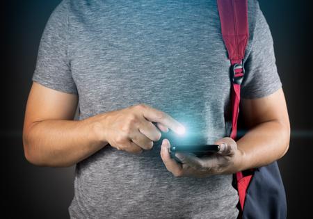 スマート フォンを使用しての社会的ネットワークと接続するアジア学生男 写真素材