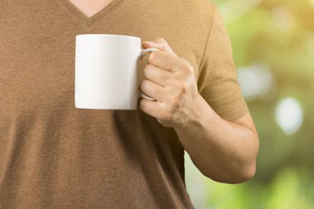 茶色の t シャツにアジア男のコーヒー カップを保持しています。良い感じ、リラックス