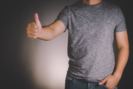 Asian man on gray t-shirt show thumb up sign Imagens