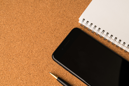 Open notebook paper with business ink pen with smart phone .flat lay style