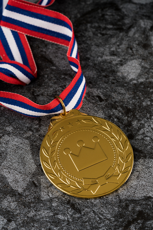 Golden medal Sport competition with red  blue and white ribbon on  black background