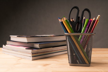 color pencil in pen pot and book on working desk Imagens
